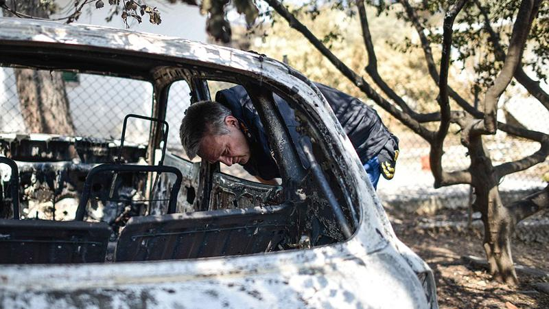 A firefighter inspects a burnt out car in the garden of a house in Mati, Greece on July 25 2018. Wildfires ravaged houses and properties in the seaside resort earlier this week, killing 79 people. | Sursa: Peter Summers